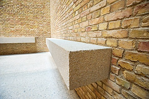 Simple stone bench  seaating and brick wall within Egyptian courtyard room of newly renovated Neues