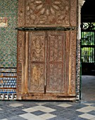 Artistic carving on old wooden door with mosaic wall,Casa Pilatos,Sevilla,Spain