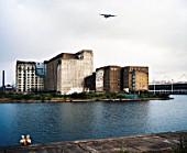 Millennium Mills, Royal Docks, East London, with approaching plane landing at City Airport