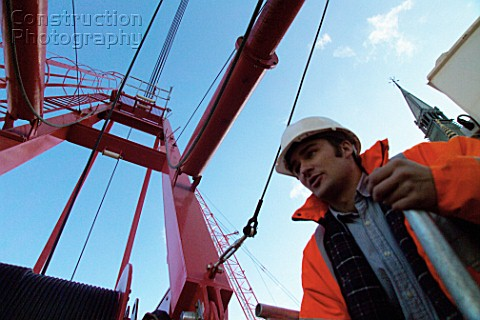Construction worker by red crane