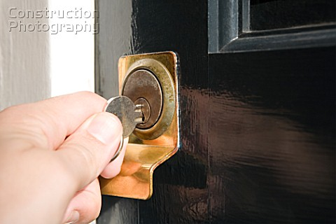 Person inserting key into lock