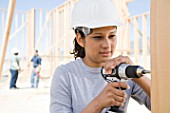 A female builder drilling
