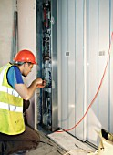 Electrician working on power supply in new building