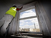 A painter restores a window frame near the BT tower in London