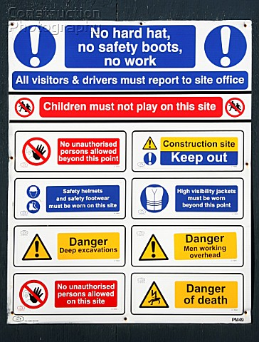 Safety sign with various warning signs outside construction of a multistory car park