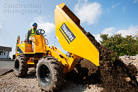 A builder driving a mini dumper truck on a house extension building job Ambleside Cumbria UK