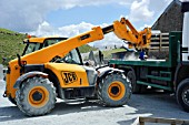 JCB telescopic forklift lifting materials from flat bed truck