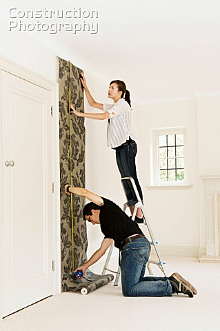 a19401087 a couple putting up wallpaper construction